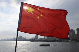 A Chinese tour boat cruises on the Yalu River behind the Chinese flag flying on the Broken Bridge, in the border city of Dandong, in China's northeast Liaoning province on September 5, 2017. The Broken Bridge once connected Dandong and the North Korean town of Sinuiju, but was bombed by the US during the Korean war and now only reaches half way across the Yalu River. / AFP PHOTO / GREG BAKER