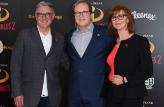 "(FILES) In this file photo taken on June 5, 2018 Producer John Walker (L), director Brad Bird and producer Nicole Paradis Grindle (R) arrive at the Disney/Pixar premiere of 'The Incredibles 2' at El Capitan theatre in Hollywood. ""Incredibles 2,"" the long-awaited return of a quirky animated superhero family from Disney-Pixar, reigned supreme at the North American box office, raking in a record $180 million in its debut, industry estimates showed June 17, 2018. It was the highest ever opening for an animated film in the US and Canada, easily besting the $135 million debut of its Disney-Pixar stablemate, ""Finding Dory"" (2016).  / AFP PHOTO / Valerie MACON"