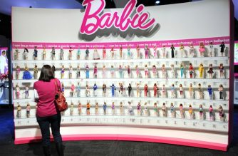 (FILES) In this file photo taken on February 14, 2010 a woman photographs a wall of Barbie dolls in the Mattel display at the annual Toy Fair in New York. / AFP Photo / Stan Honda