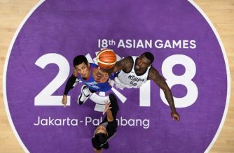 South Korea's Ricardo Preston Ratliffe (R) and the Philippines' Raymond Almazan (L) face off for the ball in the men's basketball quarter-final match between South Korea and the Philippines during the 2018 Asian Games in Jakarta on August 27, 2018.  / AFP PHOTO / Lillian SUWANRUMPHA