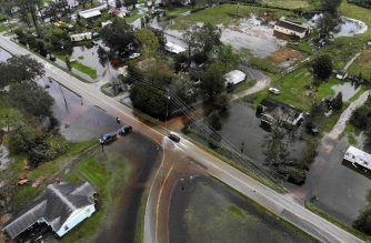 LELAND, NC- SEPTEMBER 16: A car drives down a flooded road, on September 16, 2018 in Leland, North Carolina. The state is experiencing wide spread flooding after Hurricane Florence hit area as a Category 1 storm bringing heavy wind and rain.   Mark Wilson/Getty Images/AFP
