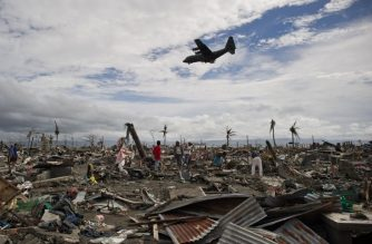 (FILES) This file photo taken on November 20, 2013 shows super typhoon Haiyan victims sifting through the rubble of their destroyed homes as a military cargo plane flies overhead in Tacoblan. - Super typhoon Haiyan struck in the predawn darkness of November 8, 2013 as the then strongest typhoon to ever hit land, leaving more than 7,360 people dead or missing across the central Philippines. (Photo by Nicolas ASFOURI / AFP)