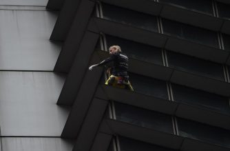 """French urban free-climber Alain Robert, popularly known as the """"French Spiderman"""", is pictured on the side of the 47-storey GT Tower in Manila's financial district of Makati on January 29, 2019. - The 56-year old adventurer climbed the 47-storey GT Tower without safety equipment, leaving watchers on the ground staring agape. (Photo by TED ALJIBE / AFP)"""