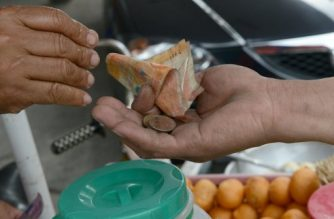 A street vendor gives Philippine peso currency change to a customer in Manila on September 13, 2012. The Philippine central bank kept its key interest rates unchanged on September 13, saying the global inflation outlook remained muted as recession flattens demand for oil and other commodities.  AFP PHOTO / JAY DIRECTO (Photo by JAY DIRECTO / AFP)
