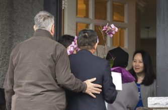 "(FILES) In this file photo taken on December 12, 2018, Meng Wanzhou (R), Chief Financial Officer of Huawei Technologies, answers the door for individuals carrying flowers after she was released on bail in Vancouver. - Canada's Justice Department on March 1, 2019 began the process of extraditing Huawei executive Weng Menzhou to the United States to face criminal charges related to alleged Iran sanctions violations. ""Today, Department of Justice Canada officials issued an Authority to Proceed, formally commencing an extradition process in the case of Ms. Meng Wanzhou,"" said a statement. (Photo by Jason Redmond / AFP)"