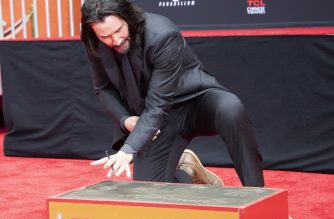 Actor Keanu Reeves signs his name in cement during his handprint ceremony at the TCL Chinese Theatre IMAX forecourt on May 14, 2019 in Hollywood, California. (Photo by VALERIE MACON / AFP)