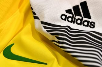 """(FILES) This file photo taken on April 25, 2018, in Paris, shows the logo of  sports wear manufacturers Nike and Adidas for the FIFA 2018 World Cup football tournament. - Adidas, Nike and PUMA on May 21, 2019, urged US President Donald Trump to prevent the shoe industry from falling victim to the trade war with China, saying new tariffs could be """"catastrophic."""" (Photo by FRANCK FIFE / AFP)"""