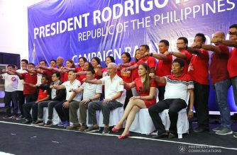 "President Rodrigo Roa Duterte strikes his signature pose with the guests during the Partido Demokratiko Pilipino-Lakas ng Bayan (PDP-Laban) campaign rally at the Garcia-Hernandez Sports and Training Center in Bohol on May 8, 2019. Seated with the President are Presidential Assistant for the Visayas Michael Dino, former Special Assistant to the President Christopher Lawrence ""Bong"" Go, former Cabinet Secretary Leoncio Evasco Jr., Garcia-Hernandez Mayor Tita Gallentes, and Bohol Second District Board Member Tomas Abapo Jr. REY BANIQUET/PRESIDENTIAL PHOTO"