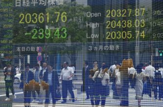 FILES: Pedestrians are reflected on an electronics stock indicator at the window of a securities company in Tokyo on June 3, 2019. (Photo by Toshifumi KITAMURA / AFP)