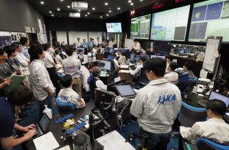 """This handout photograph taken and released by the Institute of Space and Astronautical Science (ISAS) of Japan Aerospace Exploration Agency (JAXA) on July 11, 2019 shows researchers and employees holding a briefing at the Hayabusa2 mission control room in Sagamihara city, Kanagawa prefecture. - Japan's Hayabusa2 probe neared a distant asteroid on July 11 as it descended for a final touchdown, hoping to collect samples that could shed light on the evolution of the solar system. (Photo by Yutaka IIJIMA / ISAS-JAXA / AFP) / RESTRICTED TO EDITORIAL USE - MANDATORY CREDIT """"AFP PHOTO / ISAS-JAXA"""" - NO MARKETING NO ADVERTISING CAMPAIGNS - DISTRIBUTED AS A SERVICE TO CLIENTS"""