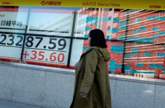 A pedestrian walks in front of an electric quotation board displaying the numbers on the Nikkei 225 index on the Tokyo Stock Exchange in Tokyo on November 6, 2019. (Photo by Kazuhiro NOGI / AFP)