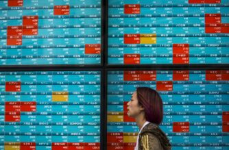 A pedestrian walks past a stock indicator displaying share prices on the Tokyo Stock Exchange in Tokyo on February 3, 2020. - Tokyo stocks dropped on February 3 as the Chinese market plunged after investors returned from an extended holiday during which the new coronavirus outbreak drove down the global market. (Photo by Behrouz MEHRI / AFP)