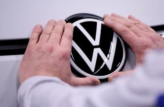 An employee of German car maker Volkswagen (VW) fixes a VW logo on the front of the Volkswagen ID.3 electric car at the Volkswagen car factory in Zwickau, eastern Germany, on February 25, 2020. (Photo by RONNY HARTMANN / AFP)