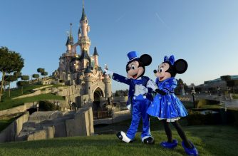 (FILES) In this file photo Disney characters Mickey and Mini mouse pose on March 16, 2017 in front of the Sleeping Beauty Castle to mark the 25th anniversary of Disneyland - originally Euro Disney Resort - in Marne-La-Vallee, east of the French capital Paris. - Disney will close its theme parks in Florida and Paris beginning Sunday March 15 due to the coronavirus, the company said, hours after announcing its California resort would shut. (Photo by BERTRAND GUAY / AFP)