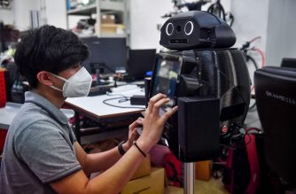 """In this photo taken on March 18, 2020 an engineering student configures a medical robot modified to screen and observe COVID-19 coronavirus patients at the Regional Center of Robotics Technology at Chulalongkorn University in Bangkok. - Thai hospitals are deploying """"ninja"""" robots to measure fevers and protect the health of overburdened medical workers on the frontlines of the coronavirus outbreak. (Photo by Lillian SUWANRUMPHA / AFP)"""
