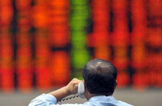 (File photo) A trader talks on the phone while in front of an electronic stocks index at the trading floor of the Philippine Stock Exchange at the financial district of Manila on September 2, 2009.  Philippine share prices closed 1.57 percent lower September 2, tracking Wall Street's retreat overnight, dealers said. The composite index lost 44.72 points to 2,808.21 while the all shares index shed 22.53 points or 1.24 percent to 1,793.67. AFP PHOTO/TED ALJIBE (Photo by TED ALJIBE / AFP)