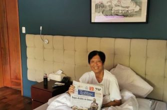 Former senator Bongbong Marcos holds up a newspaper as he sits on his bed. This picture was released by his camp to dispute circulating rumors his lung had collapsed and he had been airlifted to Singapore.