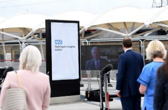 "Britain's Health Secretary Matt Hancock (C) watches a video message from Britain's Prince Charles, Prince of Walesa on a monitor during the opening of the ""NHS Nightingale"" field hospital, created at the ExCeL London exhibition centre, in London on April 3, 2020, to help with the novel coronavirus COVID-19 pandemic. - The new state-run National Health Service (NHS) hospital, named after trailblazing 19th-century nurse Florence Nightingale, has been built in just nine days. (Photo by Stefan Rousseau / POOL / AFP)"