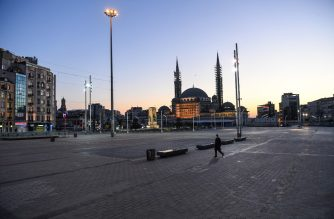 A man walks in the deserted Taksim square in Istanbul, on April 12, 2020, during a two-day curfew to prevent the spread of the epidemic COVID-19 caused by the novel coronavirus. (Photo by Ozan KOSE / AFP)