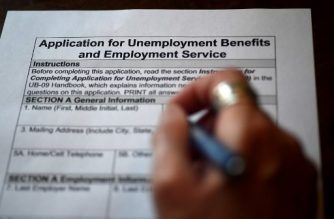 In this photo illustration, a person files an application for unemployment benefits on April 16, 2020, in Arlington, Virginia. - The government reported Thursday that another 5.2 million US workers filed for unemployment benefits, taking the four-week total to 22 million, a staggering figure in a downturn that economists say presents the country with its most severe outlook since the Great Depression of the 1930s. (Photo by Olivier DOULIERY / AFP)