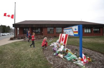 ENFIELD, NS - APRIL 20: Children lay flowers at an impromptu memorial in front of the RCMP detachment April 20, 2020 in Enfield, Nova Scotia, Canada. It was the home detachment of slain RCMP Constable Heidi Stevenson, who was one of 19 people killed during Sunday's shooting rampage, including the gunman. The rampage, which was Canada's worst mass killing, began Saturday night in Portapique, and continued through other rural communities in the Maritime Provinces.   Tim Krochak/Getty Images/AFP