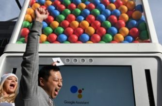 "Attendees win a gift after asking a question of Google Assistant at a giant ""Hey Google"" gumball machine game at CES 2019, January 8, 2019 at the Las Vegas Convention Center in Las Vegas, Nevada. - Google Assistant is an artificial intelligence-powered virtual assistant which can engage in two-way conversations. (Photo by Robyn Beck / AFP)"