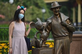 A woman wearing a face masks visits the Disneyland amusement park in Shanghai on May 11, 2020. - Disneyland Shanghai reopened on May 11 to the public after being closed since January due to the COVID-19 coronavirus outbreak. (Photo by Hector RETAMAL / AFP)