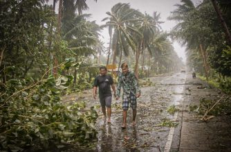 Residents brave rains and strong wind as they walk past uprooted trees along a highway in Can-avid town, Eastern Samar province, central Philippines on May 14, 2020, as Typhoon Vongfong makes landfall. - A powerful typhoon hit the central Philippines on May 14, forcing a complicated and risky evacuation for tens of thousands already hunkered down at home during the coronavirus pandemic. Because of the twin threat of the storm and the virus, evacuation centres in the central Philippines will only accept half their capacity and evacuees will have to wear facemasks. (Photo by Alren BERONIO / AFP)
