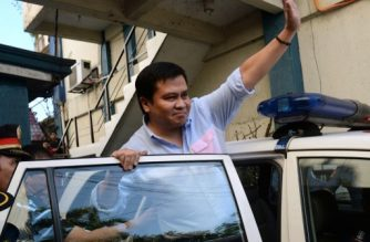 """(File photo) Philippine Senator Jose """"Jinggoy"""" Estrada (C) waves to supporters as he gets into a police car on his way to a detention center after surrendering to authorities at police headquarters in Manila on June 23, 2014.  Philippine police detained on June 23 the senator, son of former president Joseph Estrada, the second high profile official arrested within days over a massive corruption scandal.    AFP PHOTO / TED ALJIBE (Photo by TED ALJIBE / AFP)"""