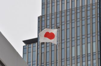 Japanese national flag flies on the roof of a building in Tokyo on November 14, 2016. - Official data showed on November 14, that Japan's economy grew a better-than-expected at 0.5 percent in the third quarter as exports offset slack consumer spending. (Photo by KAZUHIRO NOGI / AFP)