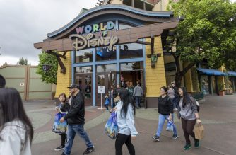 """People walk near the World of Disney store in Downtown Disney District shopping mall, which remains open on the first day of the closure of Disneyland and Disney California Adventure theme parks as fear of the spread of coronavirus continue, in Anaheim, California, on March 14, 2020. - The World Health Organization said March 13, 2020 it was not yet possible to say when the COVID-19 pandemic, which has killed more than 5,000 people worldwide, will peak. """"It's impossible for us to say when this will peak globally,"""" Maria Van Kerkhove, who heads the WHO's emerging diseases unit, told a virtual press conference, adding that """"we hope that it is sooner rather than later"""". (Photo by DAVID MCNEW / AFP)"""
