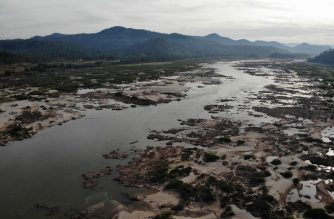 (FILES) In this aerial file photo taken on October 31, 2019 shows Mekong River in Pak Chom district in the northeastern Thai province of Loei with Laos side seen at left. - China was pressed on June 16, 2020 to be more transparent about its dam operations on the Mekong River, after water levels hit record lows last year in downstream countries which threatened the livelihoods of millions. (Photo by Lillian SUWANRUMPHA / AFP)