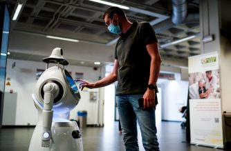 (FILES) In this file photo taken on May 29, 2020 a Belgian company ZoraBots' employee tests a robot called CRUZR at University Hospital Antwerp (UZA) in Antwerp. - This robot is set to screen hospital visitors' temperatures and detect if they are wearing masks. (Photo by Kenzo TRIBOUILLARD / AFP)