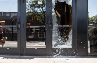 MINNEAPOLIS, MN - JUNE 21: Megan Culverhouse cleans up glass from a window shot out overnight at the Uptown Theater on June 21, 2020 in Minneapolis, Minnesota. One person was killed and 11 wounded during a melee that witnesses say was between two groups of people early Sunday morning. The wounded suffered non-life-threatening injuries, according to police.   Stephen Maturen/Getty Images/AFP