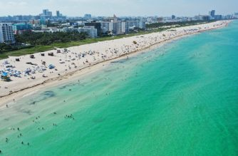 MIAMI BEACH, FLORIDA - JUNE 10: An aerial drone view as beachgoers take advantage of the opening of South Beach on June 10, 2020 in Miami Beach, Florida. Miami-Dade county and the City of Miami opened their beaches today as the area eases restrictions put in place to contain COVID-19.   Cliff Hawkins/Getty Images/AFP