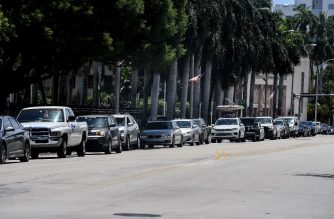 """People line up in their cars at a """"walk-in"""" and """"drive-through"""" coronavirus testing site in Miami Beach, Florida on June 24, 2020. - With coronavirus cases surging across the US South and West, officials are once again imposing tough measures, from stay-at-home advice in worst-hit states to quarantines to protect recovering areas like New York. Nearly four months after the United States reported its first death from COVID-19, the nation faces a deepening health crisis as a wave of infections hits young Americans and experts issue new acute warnings. (Photo by CHANDAN KHANNA / AFP)"""