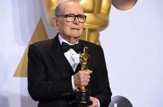 """(FILES) In this file photo taken on February 28, 2016 Italian composer Ennio Morricone poses with the Oscar for Best Original Score, """"The Hateful Eight,"""" in the press room during the 88th Oscars in Hollywood. - Ennio Morricone, one of the world's best-known and most prolific film composers, has died in Rome, Italian media reported on July 6, 2020. (Photo by Robyn BECK / AFP)"""