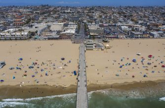 An aerial view shows people on the beach during a heatwave as coronavirus cases reach new record levels in states across the nation, in Hermosa Beach, California, on July 12, 2020. - Los Angeles County beaches are reopened after they were re-closed over the Fourth of July weekend because of fears that large gatherings would further accelerate the spread of COVIC-19. More than 2,000 people are currently hospitalized with COVID-19 in Los Angeles County. (Photo by DAVID MCNEW / AFP)