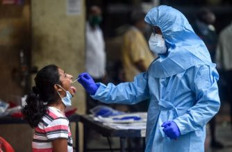 A health worker (R) takes a swab sample from a resident getting tested for the COVID-19 coronavirus near residential buildings in Mumbai on July 16, 2020. (Photo by Punit PARANJPE / AFP)