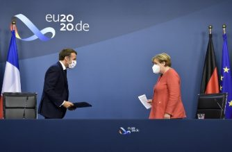 German Chancellor Angela Merkel (R) and French President Emmanuel Macron (L) leave after their joint video press conference at the end of the European summit at the EU headquarters in Brussels on July 21, 2020. - EU leaders approved a 750-billion-euro package to revive their coronavirus-ravaged economies after a tough 90-hour summit on July 21, along with a trillion-euro budget for the next seven years. (Photo by JOHN THYS / POOL / AFP)