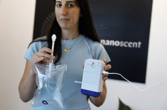 "An employee holds a coronavirus breathalyser test at the laboratory of NanoScent's headquarters in Misgav industrial zone near the northern Israeli city of Karmiel, on July 21, 2020. - An Israeli company is developing a coronavirus breathalyser test that gives results in 30 seconds, billing it as a ""front line"" tool that can help restore a sense of normalcy during the pandemic. NanoScent, the firm making the test kits, said an extensive trial in Israel delivered results with 85 percent accuracy, and the product could receive regulatory approval within months. (Photo by MENAHEM KAHANA / AFP)"