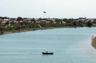 A man paddles a boat on the Kura river on July 5, 2020. - The village of Banka should have plentiful supplies, since it lies beside one of the Caspian country's mightiest rivers, the Kura. But the river has shallowed dramatically in Azerbaijan this summer and has become contaminated with salty seawater, with experts warning of an ecological disaster unfolding. (Photo by TOFIK BABAYEV / AFP)