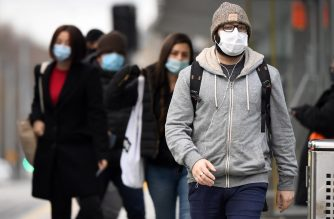 Commuters walk past Melbourne's Flinders Street Station on July 23, 2020 on the first day of the mandatory wearing of face masks in public areas as the city experiences an outbreak of the COVID-19 coronavirus. (Photo by William WEST / AFP)