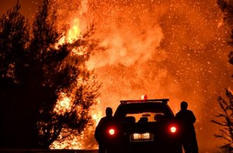 Firefighters stand near a pine forest wildfire fanned by strong winds near the village of Athikia, in Peloponnese area near Corinth late on July 22, 2020. - Greek authorities evacuated five settlements as a precaution. Summer fires are frequent in Greece, with temperatures regularly over 30 degrees Celsius (86 degrees Fahrenheit). In July 2018 a fire left 102 people dead in the worst such tragedy in modern Greek history, in Mati, a coastal resort northeast of Athens. (Photo by Valerie GACHE / AFP)