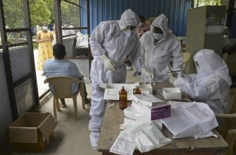 Health workers wearing Personal Protective Equipment (PPE) gear prepare to collect swab samples of residents at a free testing centre for the COVID-19 coronavirus, at Ranga Reddy district on the outskirts of Hyderabad on July 24, 2020. - India's death toll from the novel coronavirus overtook France's on July 24 with 30,601 fatalities and nearly 50,000 new cases overnight, official data showed. (Photo by NOAH SEELAM / AFP)