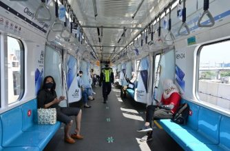 Passengers sit on designated seats to ensure physical distancing as they travel on a Mass Rapid Transit (MRT) system train in Jakarta on July 26, 2020. (Photo by ADEK BERRY / AFP)