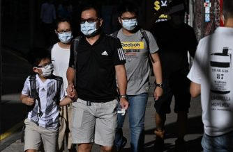 Pedestrians wearing face masks walk along a pavement in Hong Kong on July 27, 2020. - Everyone in Hong Kong will have to wear masks in public from this week, authorities said on July 27, as they unveiled the city's toughest social distancing measures yet to combat a new wave of COVID-19 coronavirus infections. (Photo by Anthony WALLACE / AFP)