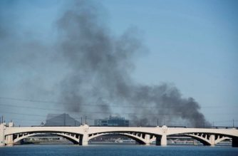 Smoke can be seen from a train derailment and fire along a bridge over Tempe Town Lake in Tempe, Arizona July 29, 2020. - A train derailed and caught fire early in the morning on a bridge in Arizona that partially collapsed. Union Pacific said the freight train derailed around 6:15am local time and that eight to 10 rail cars were on fire. It said the south side of the bridge, which extends over Tempe Town Lake near Phoenix, collapsed, and rail cars fell into an empty park below. (Photo by Laura Segall / AFP)