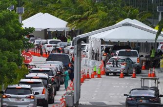 "(FILES) In this file photo cars line up for Covid-19 test at a ""walk-in"" and ""drive-through"" coronavirus testing site in Miami Beach, Florida on July 22, 2020. - Florida registered a record 253 coronavirus deaths on July 30, 2020, setting a grim new high for the third day in a row as the state closes down some COVID-19 test centers due to a looming tropical storm.The state's daily toll has leapt over the last week, bringing the overall deaths to 6,586, according to the Florida department of health. (Photo by CHANDAN KHANNA / AFP)"