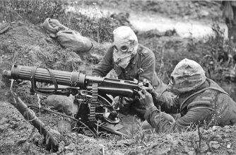 British Vickers machine gun crew wearing PH-type anti-gas helmets. Near Ovillers during the Battle of the Somme, July 1916. The gunner is wearing a padded waistcoat, enabling him to carry the machine gun barrel/Courtesy Imperial War Museums collection. This is photograph Q 3995 from the collections of the Imperial War Museums (collection no. 1900-13)/Public Domain photo